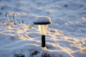 snowy solar garden lamp in winter time