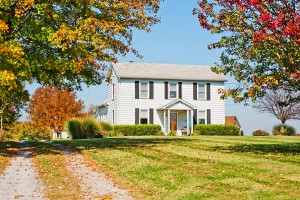 Two story white wood siding farm house in USA in autumn.